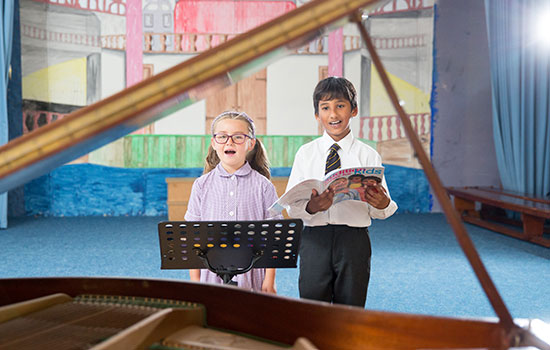 children singing with piano in foreground