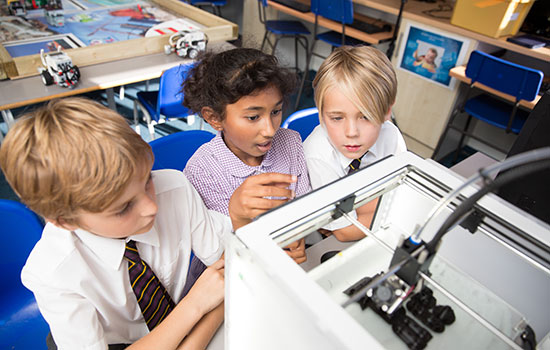 school children looking at 3d printer